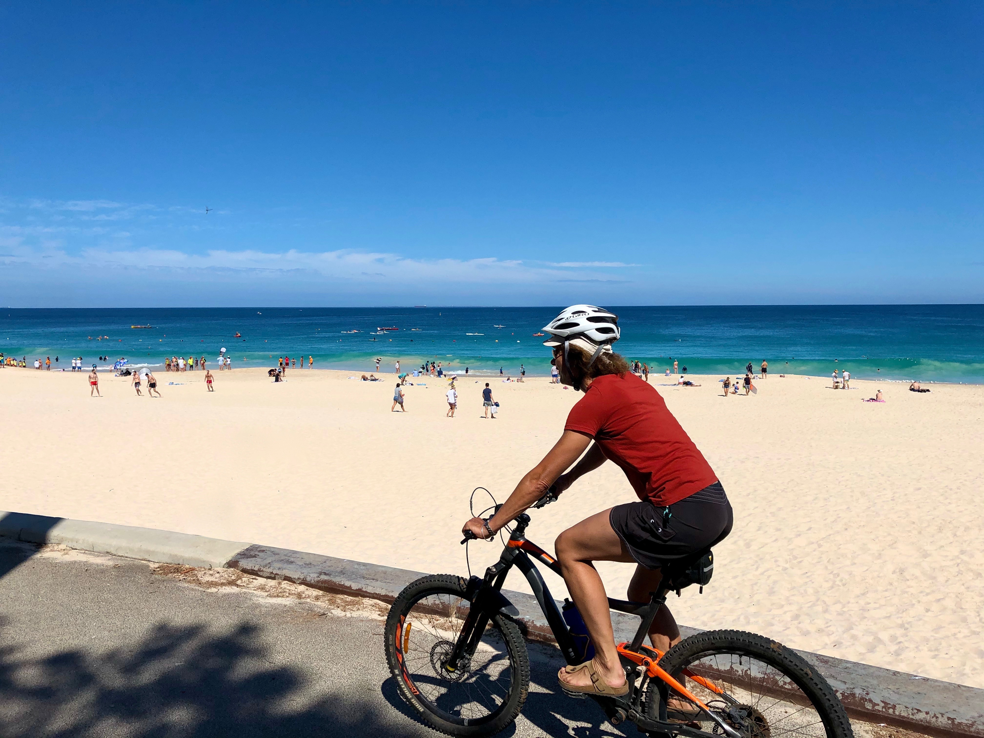 A cyclist riding along the City Beach foreshore